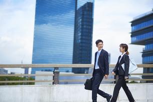外を歩いているスーツを着た男性と女性の写真素材 [FYI04581237]