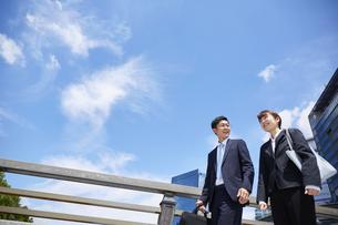外を歩いているスーツを着た男性と女性の写真素材 [FYI04581238]