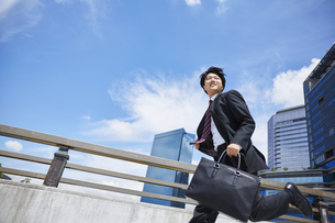 スーツを着て走っているビジネスマンの写真素材 [FYI04581239]