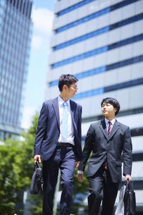 並んで歩くスーツを着たビジネスマンの写真素材 [FYI04581243]