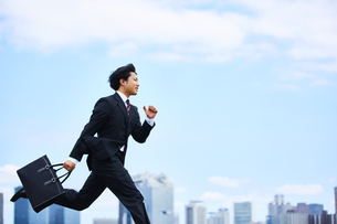 スーツを着て走っているビジネスマンの写真素材 [FYI04581247]