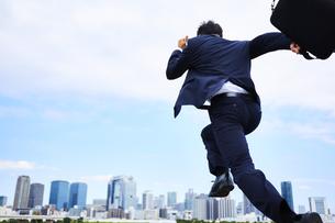 スーツを着て走っているビジネスマンの写真素材 [FYI04581250]