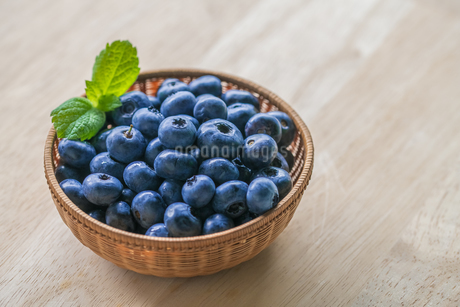 Fresh ripe blueberries in basket on wooden background.の写真素材 [FYI04581754]