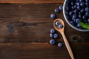 Fresh ripe blueberries in spoon on wooden background.の写真素材 [FYI04582384]
