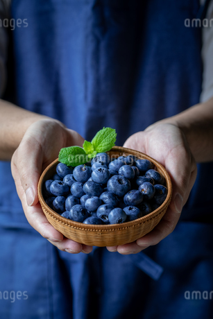 Man holds a wicker basket of blueberries.の写真素材 [FYI04582437]