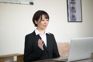 パソコンに向かって話をしているスーツ姿の女性の写真素材 [FYI04582719]