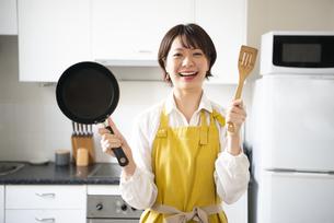 キッチンでポーズを取っているエプロン姿の女性の写真素材 [FYI04582770]