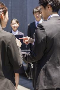 パソコンを見るビジネスマンと見守る新入社員の写真素材 [FYI04582807]