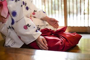 風呂敷包みに手を添える浴衣の女性の写真素材 [FYI04583026]