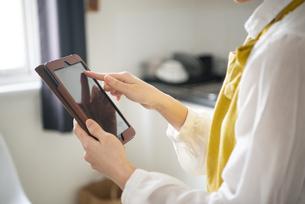 タブレットでレシピ検索をしている女性の手元の写真素材 [FYI04583276]