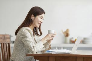 イヤホンをしてオンライン会議をする働く女性の写真素材 [FYI04583483]