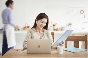 イヤホンをしてオンライン会議をする働く女性の写真素材 [FYI04583493]