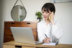 パソコンの前で電話をしている女性の写真素材 [FYI04584341]