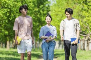 会話をしながら歩く若者グループの写真素材 [FYI04584372]