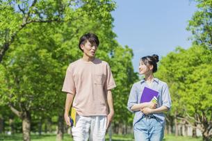 会話をしながら歩く若者2人組の写真素材 [FYI04584377]