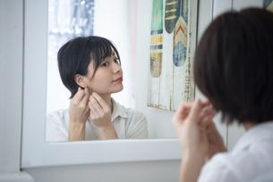 鏡を見ながらピアスをつけている女性の写真素材 [FYI04584457]