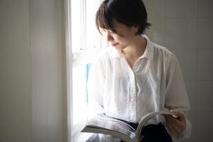 本を開いて外を見ている女性の写真素材 [FYI04584465]