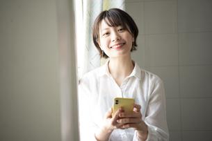 スマホを持って笑っている女性の写真素材 [FYI04584473]