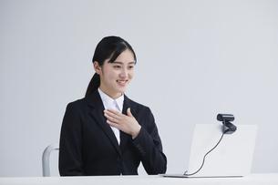ノートパソコンの前でカメラに向かって話すスーツを着た若い女性の写真素材 [FYI04587148]