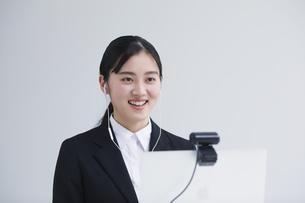 ノートパソコンの前でカメラに向かって話すスーツを着た若い女性の写真素材 [FYI04587153]