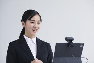 パソコンの前でカメラに向かって話すスーツを着た若い女性の写真素材 [FYI04587157]