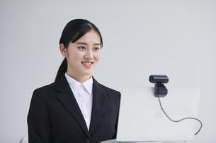 ノートパソコンの前でカメラに向かって話すスーツを着た若い女性の写真素材 [FYI04587159]