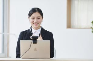 ノートパソコンの前でカメラに向かって話すスーツを着た若い女性の写真素材 [FYI04587174]