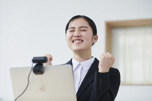 ノートパソコンの前でカメラに向かって話すスーツを着た若い女性の写真素材 [FYI04587185]