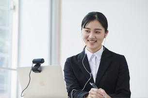 ノートパソコンの前でカメラに向かって話すスーツを着た若い女性の写真素材 [FYI04587186]