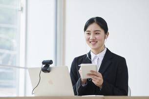 ノートパソコンの前でカメラに向かって話すスーツを着た若い女性の写真素材 [FYI04587188]