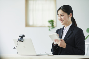 ノートパソコンの前でカメラに向かって話すスーツを着た若い女性の写真素材 [FYI04587191]