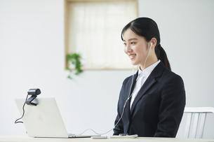 ノートパソコンの前でカメラに向かって話すスーツを着た若い女性の写真素材 [FYI04587193]