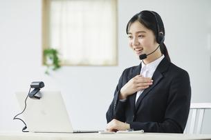 ノートパソコンのカメラに向かって話すインカムをした笑顔のスーツを着た若い女性の写真素材 [FYI04587230]
