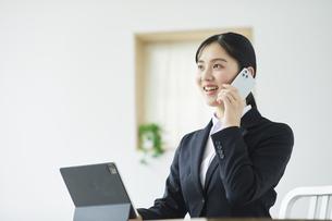 タブレット端末を使いながらスマートフォンを持つ笑顔のスーツを着た若い女性の写真素材 [FYI04587243]