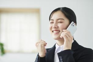 スマートフォンを持ち喜ぶスーツを着た若い女性の写真素材 [FYI04587246]