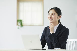ノートパソコンを使うスーツを着た若い女性の写真素材 [FYI04587251]