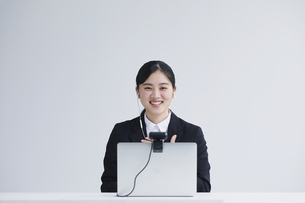 ノートパソコンのカメラに向かって話す笑顔のスーツを着た若い女性の写真素材 [FYI04587357]