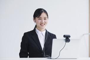 ノートパソコンのカメラに向かって話す笑顔のスーツを着た若い女性の写真素材 [FYI04587363]