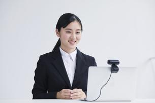 ノートパソコンのカメラに向かって話す笑顔のスーツを着た若い女性の写真素材 [FYI04587364]