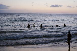 夕暮れ時の海と人のシルエットの写真素材 [FYI04587547]
