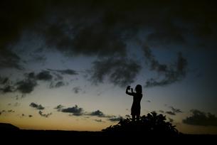 夕闇を撮影する人のシルエットの写真素材 [FYI04587549]