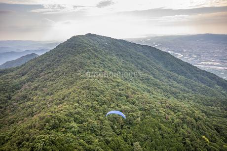 龍門山の稜線上を飛ぶパラグライダーを空撮の写真素材 [FYI04587662]
