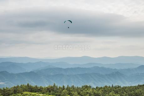龍門山頂から稜線の上を飛ぶパラグライダーを空撮の写真素材 [FYI04587663]