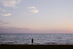夕暮れ時の海と人のシルエットの写真素材 [FYI04587877]