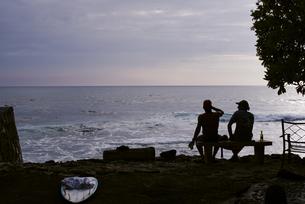 夕暮れ時の海と人のシルエットの写真素材 [FYI04587890]