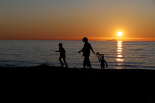 日没前の浜辺 親子連れのシルエットの写真素材 [FYI04588250]