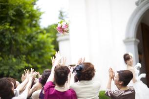 花嫁が投げたブーケをキャッチしようとする友人達の写真素材 [FYI04588648]