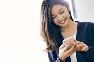 スマートフォンを見る30代ビジネスウーマンの写真素材 [FYI04589647]