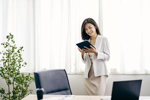 タブレットPCを見る30代ビジネスウーマンの写真素材 [FYI04589882]