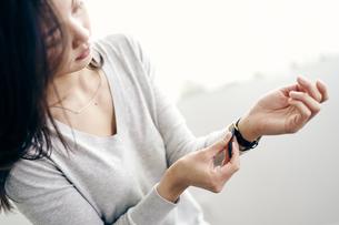 腕時計をつける女性の写真素材 [FYI04589894]